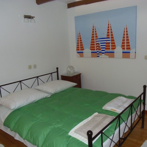 bed and Tomislav Ostrman's painting in master bedroom